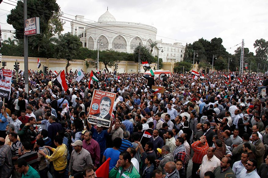 Supporters of Egyptian President Mohammed Morsi chant slogans and wave his campaign posters outside the Presidential palace, background, in Cairo, Egypt, Friday, Nov. 23, 2012. Supporters and opponents of Egypt's Islamist president staged rival rallies Friday after he assumed sweeping new powers, a clear show of the deepening polarization plaguing the country.(AP Photo/Ahmed Abd el Fatah)