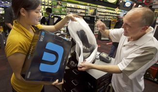 GameStop employee Lani Girran hands over a Wii U system to Kevin Owande, 51, of Renton, Wash., on a busy Black Friday at the GameStop Southcenter store in Seattle on Nov. 23, 2012. Owande was up early on Black Friday to purchase Wii U, one of the hottest products this holiday season. (Stephen Brashear/Invision for Nintendo/Associated Press)