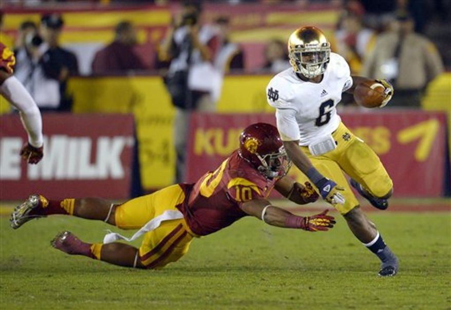 Notre Dame running back Theo Riddick, right, breaks the tackle of Southern California linebacker Hayes Pullard during the first half of an NCAA college football game, Saturday, Nov. 24, 2012, in Los Angeles. (AP Photo/Mark J. Terrill)