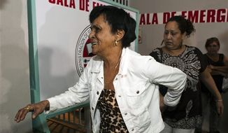"Maria Matias, left, mother of former world boxing champion Hector ""Macho"" Camacho, walks to attend a news conference outside Centro Medico trauma center in San Juan, Puerto Rico, Friday, Nov. 23, 2012. Camacho, who has been unconscious since he was shot in the face last Tuesday and declared brain dead by doctors, will be taken off life support on Saturday, his mother said in the brief news conference, a decision that the former championship boxer's eldest son opposes. (AP Photo/Dennis M. Rivera Pichardo)"