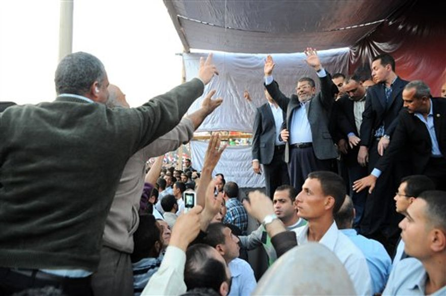 """In this Friday, Nov. 23, 2012 photo released by the Egyptian Presidency, President Mohammed Morsi, center right, waves to supporters outside the Presidential palace in Cairo, Egypt. Egypt's official news agency says that the country's highest body of judges has called the president's recent decrees an """"unprecedented assault on the independence of the judiciary and its rulings."""" In a statement carried on MEAN Saturday, the Supreme Judicial Council says they regret the declarations President Mohammed Morsi issued Thursday.(AP Photo/Egyptian Presidency)"""