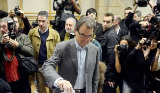 Artur Mas, the leader of center-right Catalan Nationalist Coalition, votes during Sunday's elections. He is in a power struggle over Catalonia with Prime Minister Mariano Rajoy (left). (Associated Press)