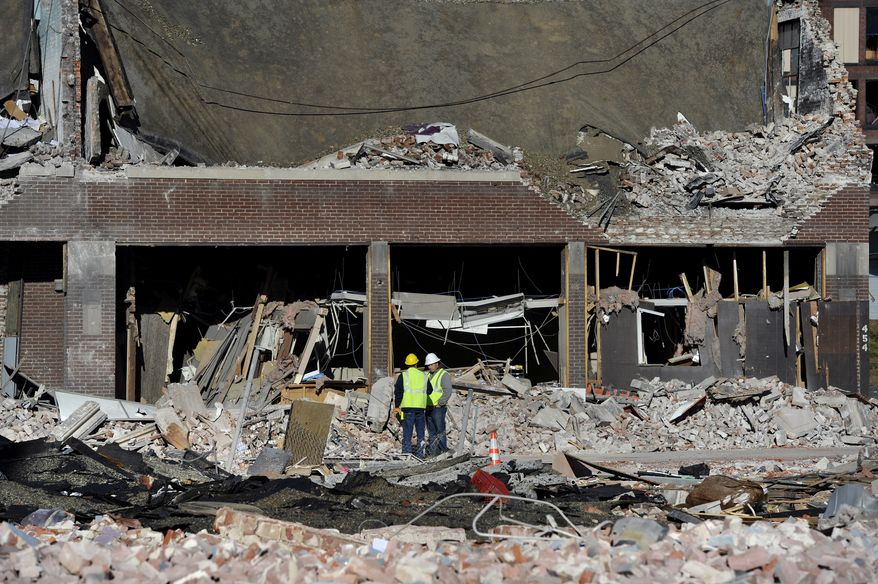 Inspectors stand in debris on Saturday, Nov. 24, 2012, at the site of a natural-gas explosion that leveled a strip club in Springfield, Mass., on Friday evening. (AP Photo/Jessica Hill)