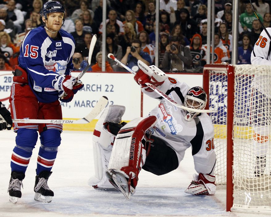 New York Team's Jeff Halpern (15) skates near as New Jersey Team goalie Martin Brodeur falls in front of the net during the first period of a charity hockey game in Atlantic City, N.J., Saturday, Nov. 24, 2012. (AP Photo/Mel Evans)