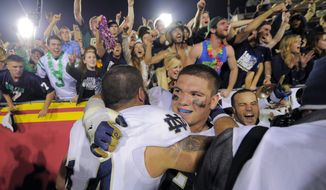Notre Dame linebacker Carlo Calabrese, left, celebrates with center Braxston Cave after Notre Dame defeated Southern California 22-13 in an NCAA college football game, Saturday, Nov. 24, 2012, in Los Angeles. (AP Photo/Mark J. Terrill)