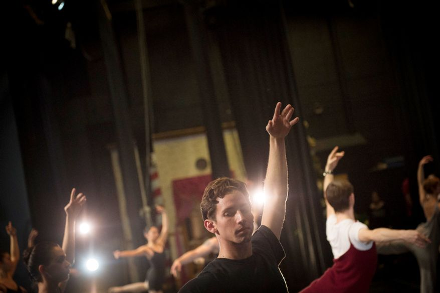 Dancer Nolan Seda, with the City of San Diego Ballet, warms up on stage prior to their performance of The Nutcracker at W.T. Woodson High School in Fairfax, Va., Sunday, Nov. 25, 2012.  (Rod Lamkey Jr./The Washington Times)
