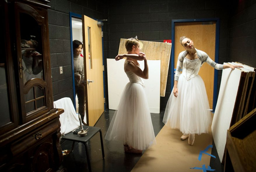 Dancers Ariane Georg (left) and Emily Bond (right) stretch in a side room off stage prior to their performance of The Nutcracker at W.T. Woodson High School in Fairfax, Va., Sunday, Nov. 25, 2012. (Rod Lamkey Jr./The Washington Times)
