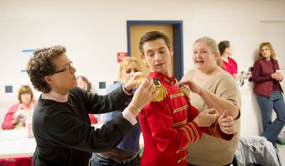 Dancer Alexandru Glusacov gets help with his uniform prior to their performance of The Nutcracker at W.T. Woodson High School presented by the Fairfax Ballet 2012. (Rod Lamkey Jr./The Washington Times)