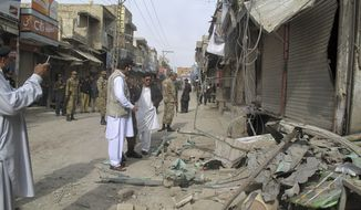 Pakistani security officials check the site of a bomb blast as the minority Muslim Shiite sect observed the annual Ashoura holiday in Dera Ismail Khan, Pakistan, on Sunday, Nov. 25, 2012. (AP Photo/Kashif Naveed)