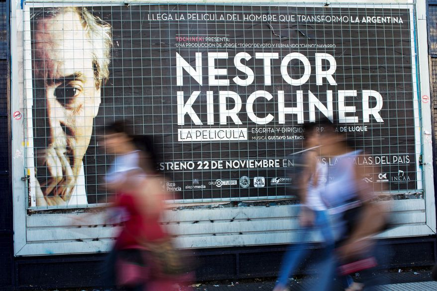 "People walk by a banner promoting the documentary film ""Nestor Kirchner"" in Buenos Aires, Argentina, Wednesday, Nov. 21, 2012. The film hits the theaters on Thursday, the latest example of an ongoing effort to exalt the late president's memory, seeking to match the level of Juan Domingo Peron. Streets, hospitals, tunnels and even a soccer tournament is named after Nestor Kirchner, who served as president from 2003 to 2007 and died at the age of 60 on Oct. 27, 2010. (AP Photo/Natacha Pisarenko)"