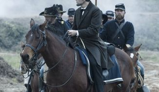 """Actor Daniel Day-Lewis, portraying President Abraham Lincoln, looks across a battlefield in the aftermath of a terrible siege in a scene from director Steven Spielberg's biopic """"Lincoln."""" (Dreamworks/Twentieth Century Fox)"""