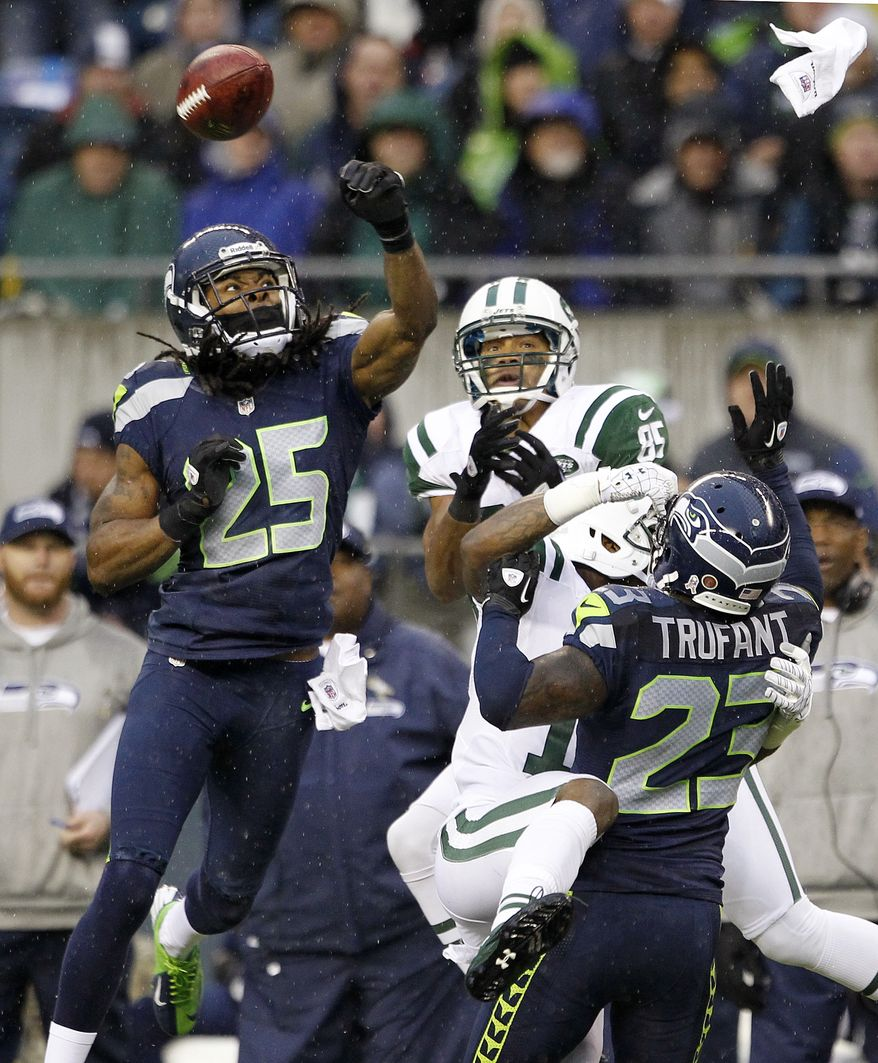 Seattle Seahawks' Richard Sherman (25) knocks the ball away from New York Jets' Chaz Schilens (85) as Seahawks' Marcus Trufant (23) collides with Jets' Jeremy Kerley during the second half of an NFL football game, Sunday, Nov. 11, 2012, in Seattle. The Seahawks won 28-7. (AP Photo/Elaine Thompson)