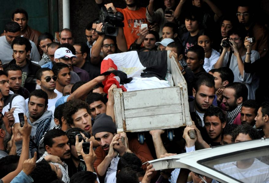 Egyptians carry the body of Gaber Salah, who was killed in clashes with security forces, during his funeral procession in Cairo on Monday, Nov. 26, 2012. Thousands marched through Tahrir Square, the birthplace of last year's uprising that toppled authoritarian leader Hosni Mubarak, for the funeral of Mr. Salah. (AP Photo/Hussein Tallal)
