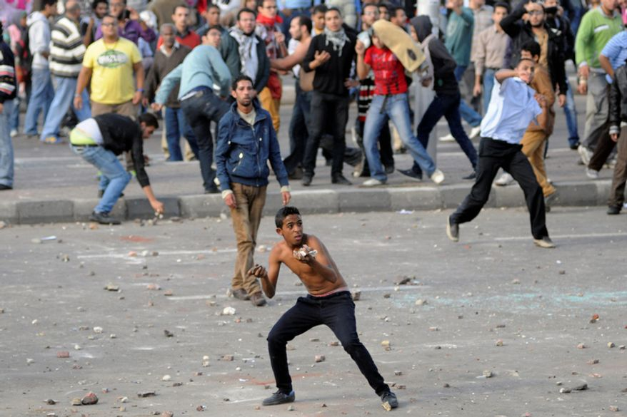 Protesters hurl stones during clashes between supporters and opponents of President Mohammed Morsi in Alexandria, Egypt, on Friday, Nov. 23, 2012. Opponents and supporters of Mr. Morsi clashed across Egypt on Friday, the day after the president granted himself sweeping new powers that critics fear can allow him to be a virtual dictator. Thousands from the two camps threw stones and chunks of marble at one another outside a mosque in the Mediterranean city after Friday's Muslim prayers. (AP Photo/Tarek Fawzy)