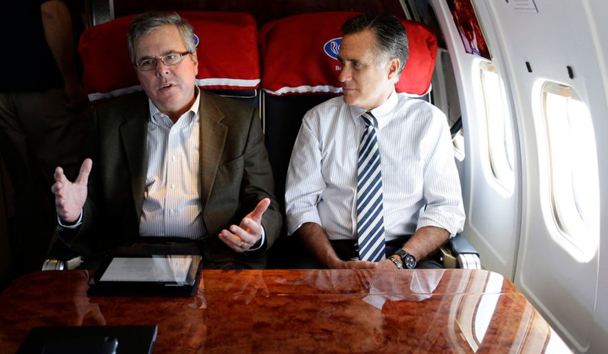 Republican presidential candidate Mitt Romney (right) talks with former Florida Gov. Jeb Bush as they fly on Mr. Romney's campaign plane to Miami on Wednesday, Oct. 31, 2012. (AP Photo/Charles Dharapak) ** FILE **