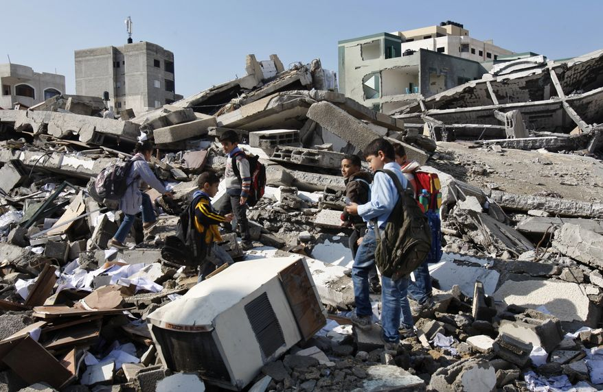 On Monday, Nov. 26, 2012, Palestinian schoolchildren walk in the rubble left days after an Israeli airstrike destroyed the Hamas Interior Ministry in Gaza City, Gaza Strip. (AP Photo/Adel Hana)