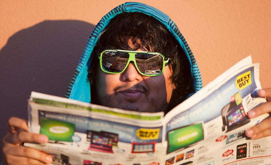 Renzo Zapata, 26, of Springfield, Va., looks over deals while waiting in line at Best Buy on Thanksgiving Day, Thursday, Nov. 22, 2012, in Springfield. One family waited in line starting Tuesday night to be the first customers. (Craig Bisacre/The Washington Times)