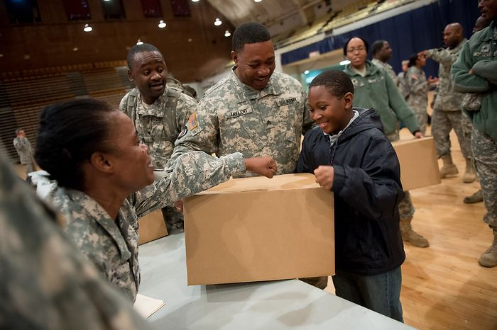 National Guard Sgt. Cliffy Taylor (center) picks up a Thanksgiving turkey and side dishes with his son, Cliffy Taylor Jr., 9, at the D.C. Armory in Washington on Tuesday, Nov. 20, 2012. Harris Teeter supermarket and Miller/Coors brewery donated 400 Thanksgiving meals as part of Operation Homefront, which provides assistance to military families and wounded warriors. (Andrew Harnik/The Washington Times)