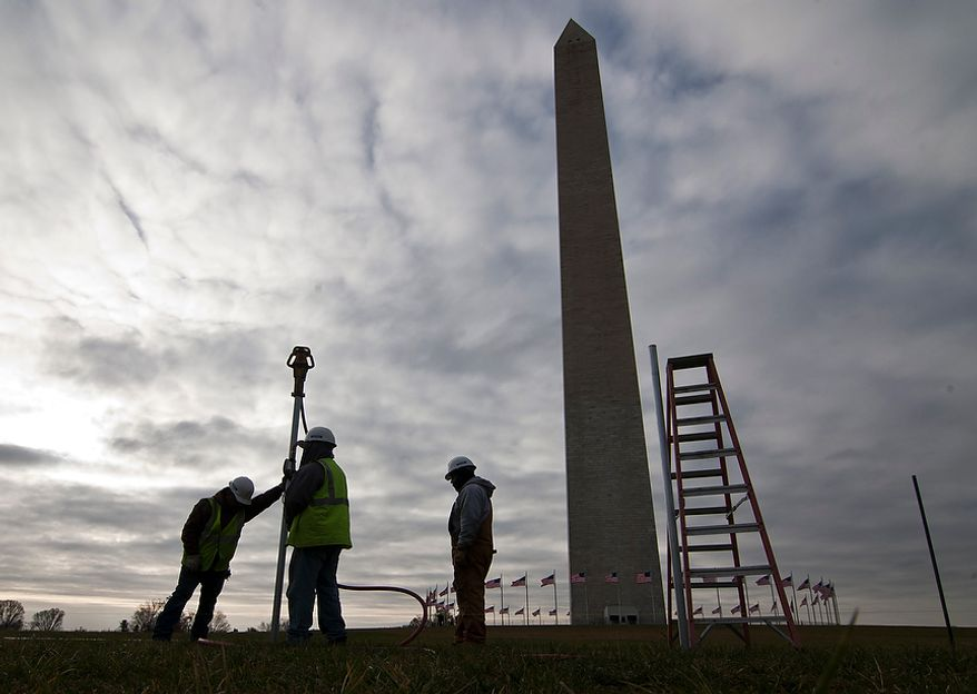 Construction crews start work on the 1,000-yard outer fence that will run along the perimeter of the Washington Monument in Washington on Monday, Nov. 19, 2012. The monument has been closed since Aug. 25, 2011, when a 5.8-magnitude earthquake occurred less than 100 miles southwest of the city. The repairs will occur in conjunction with the Mall Renovation Project that was already scheduled. The scaffolding and construction work will start soon after the fence is in place. (Craig Bisacre/The Washington Times)