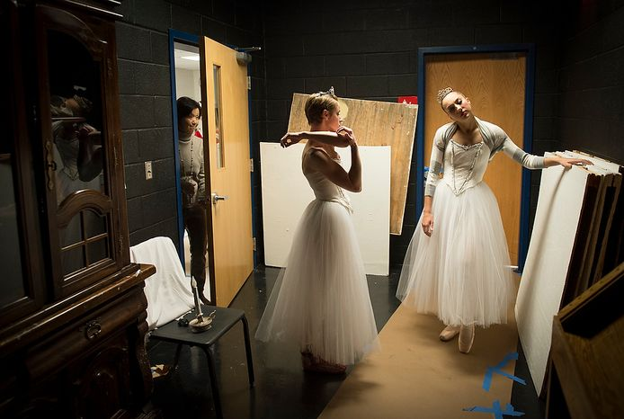 """Dancers Ariane George (left) and Emily Bond (right) stretch in a side room offstage before their performance of """"The Nutcracker"""" at W.T. Woodson High School in Fairfax, Va., on Sunday, Nov. 25, 2012. This is the final day of the show, which is presented by the Fairfax Ballet 2012. (Rod Lamkey Jr./The Washington Times)"""