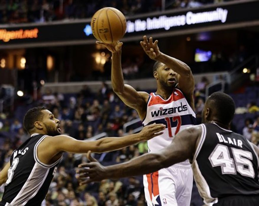 San Antonio Spurs guard Patty Mills (8) and center DeJuan Blair (45) guard Washington Wizards guard A.J. Price as he passes the ball in the first half of an NBA game Monday, Nov. 26, 2012, in Washington.(AP Photo/Alex Brandon)