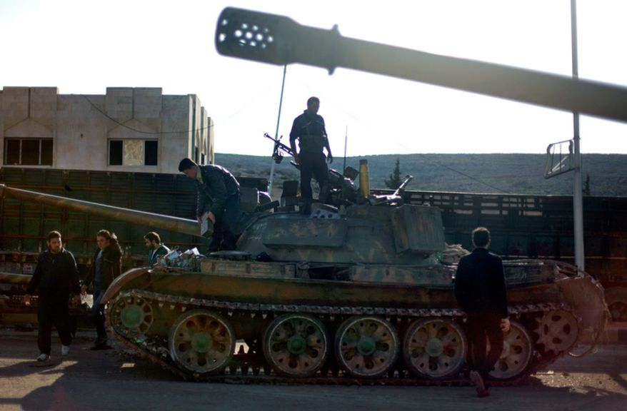 Syrian fighters check a tank they took after storming a military base in Aleppo, Syria, on Monday, Nov. 19, 2012. (AP Photo/Khalil Hamra)