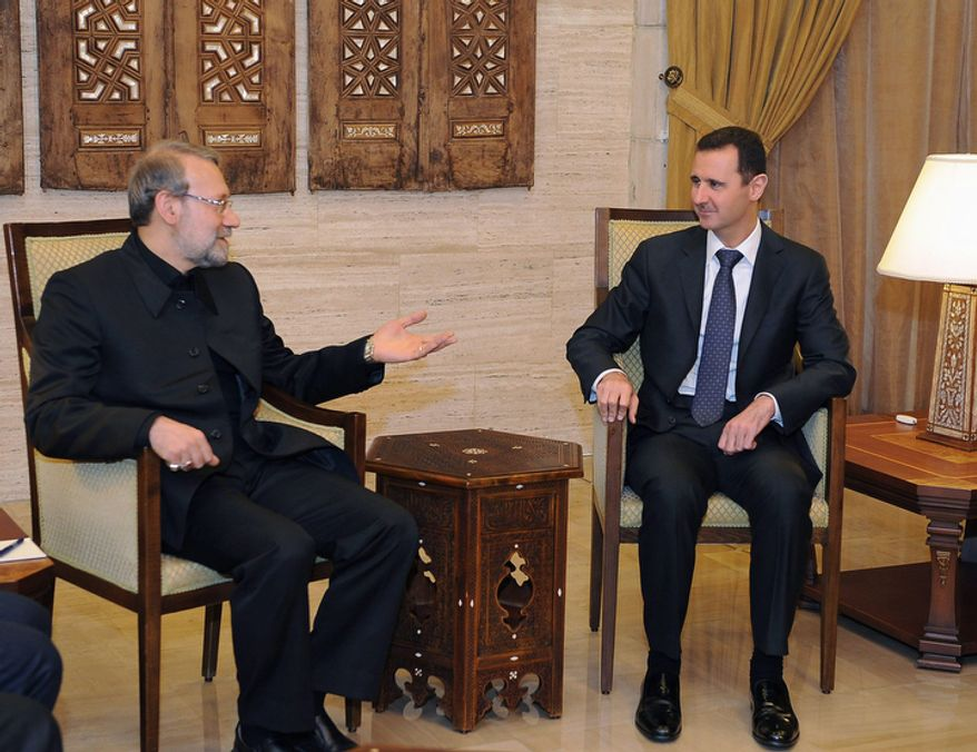 In this photo released by the official Syrian news agency, SANA, Syrian President Bashar Assad (right) meets with the speaker of the Iranian parliament, Ali Larijani (left), in Damascus, Syria, on Friday Nov. 23,  2012. Mr. Larijani was in Damascus to hold talks with Mr. Assad and other officials before flying on to neighboring Lebanon. (AP Photo/SANA)