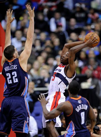 Washington Wizards guard Jordan Crawford (15) goes to the basket against Charlotte Bobcats center Byron Mullens (22) and Ben Gordon (8) during the first half of an NBA basketball game on Saturday, Nov. 24, 2012, in Washington. (AP Photo/Nick Wass)