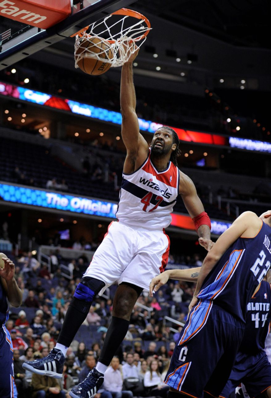 Washington Wizards center Nene (42), of Brazil, dunks against Charlotte Bobcats center Byron Mullens (22) during the first overtime period of an NBA basketball game on Saturday, Nov. 24, 2012, in Washington. Charlotte won 108-106. (AP Photo/Nick Wass)
