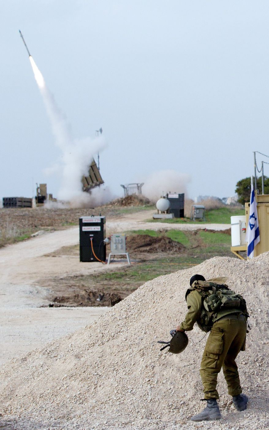 ** FILE ** In this 2012 file photo, an Israeli soldier reacts as an intercepting missile is launched near the city of Ashdod, Israel. (Associated Press)