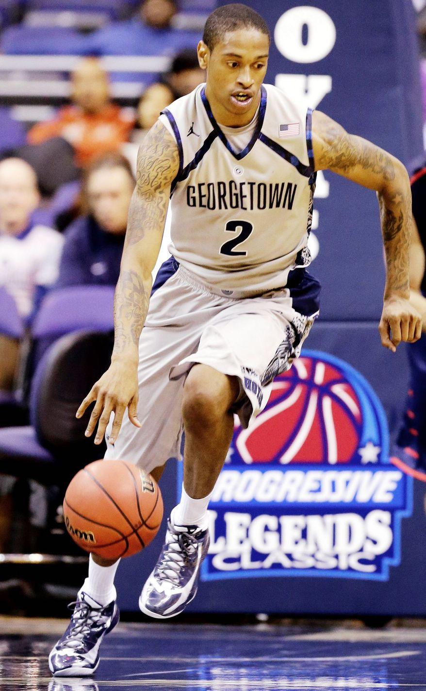 Georgetown forward Greg Whittington, left, dribbles the ball as he pursued by Liberty forward JR Coronado during the second half of an NCAA college basketball game on Wednesday, Nov. 14, 2012, in Washington. Georgetown won 68-59. (AP Photo/Alex Brandon)