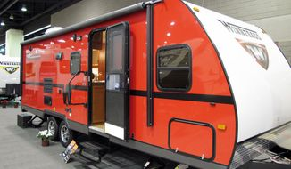 Recreational-vehicle maker Winnebago shows off its Minnie towable RV at a trade show Tuesday in Louisville, Ky. Cash-conscious consumers are choosing less-expensive RVs that are hitched to the backs of other vehicles. (Associated Press)
