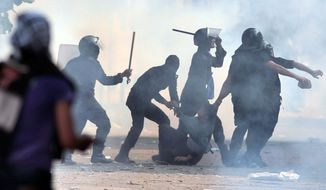 Egyptian security forces arrest a protester on his way to the anti-Morsi rally in Cairo. (Associated Press)