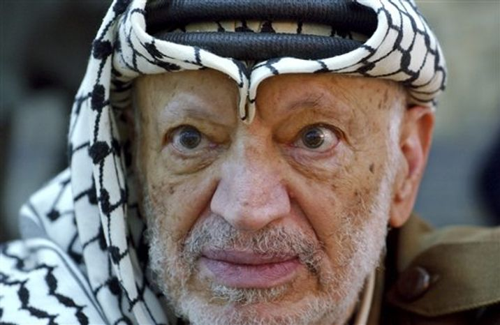 ** FILE ** In this Saturday, Oct. 2, 2004, file photo, Palestinian leader Yasser Arafat pauses during an emergency cabinet session, at his compound, in the West Bank town of Ramallah. The remains of former Palestinian leader Yasser Arafat were exhumed on Tuesday, Nov. 27, 2012, to enable foreign experts to take samples as part of a probe into his death. (AP Photo/Muhammed Muheisen, File)