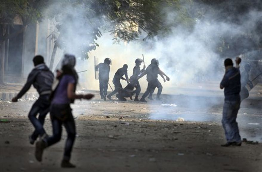 Egyptian security forces arrest a protester during clashes near Tahrir square, where an opposition rally has been called for to voice rejection of President Morsi's seizure of near absolute powers, in Cairo, Egypt, Tuesday, Nov. 27, 2012. (AP Photo/ Khalil Hamra)