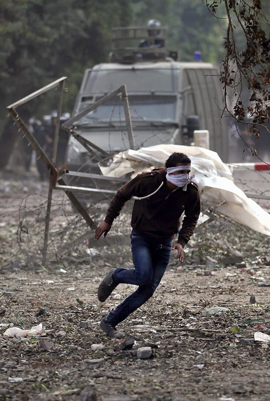 An Egyptian protester runs for cover during clashes with security forces near Tahrir Square in Cairo on Tuesday, Nov. 27, 2012. Demonstrators and police clashed just hours ahead of a planned mass rally by opponents of the country's Islamist president, who are demanding he rescind decrees that granted him near-absolute powers. (AP Photo/Khalil Hamra)