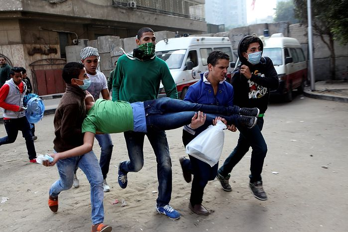 Egyptians carry  a protester wounded in clashes with security forces near Tahrir Square, where an opposition rally has been called to voice rejection of President Mohammed Morsi's seizure of near-absolute powers, in Cairo on Tuesday, Nov. 27, 2012. The Health Ministry said about 444 people have been wounded nationwide, including 49 who remain hospitalized, since the clashes erupted on Friday, according to a statement carried by the official news agency, MENA. (AP Photo/Thomas Hartwell)