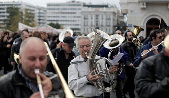 Musicians from a municipal band play during a protest march to the ministry of Administrative Reform in central Athens, Tuesday, Nov. 27, 2012. Several hundred people took part in the peaceful demonstration. Greek municipal workers have occupied hundreds of town halls across the country to protest against government plans to suspend 2,000 civil servants for potential dismissal due to state budget cuts. (AP Photo/Petros Giannakouris)