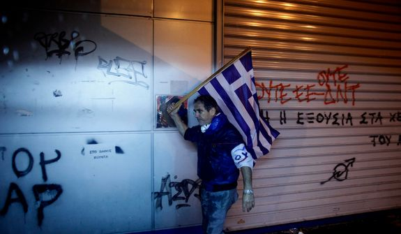 "A protester holding a Greek national flag walks next to graffiti reading ""Power at the peoples hands "" during clashes in front of the Greek parliament in Athens, Wed. Nov.7 2012. (AP Photo/Kostas Tsironis)"