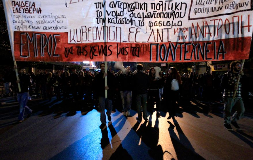 """Protesters march during a protest commemorating the student uprising against a military dictatorship in 1973, at the northern city of Thessaloniki, Greece, Saturday, Nov. 17 2012. The banner is reading """"Against Government - IMF - EU. (AP Photo/Nikolas Giakoumidis)"""