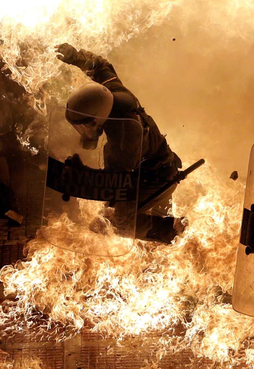 A riot police officer is engulfed by petrol bomb flames thrown by protesters in front of the parliament during clashes in Athens on Wednesday Nov. 7, 2012. Greece's fragile coalition government faces its toughest test so far when lawmakers vote later Wednesday on new painful austerity measures demanded to keep the country afloat, on the second day of a nationwide general strike. (AP Photo Dimitri Messinis)