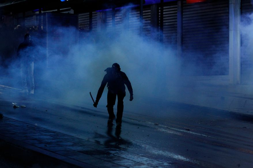 A protester appears from a tear gas cloud during clashes in front of the Greek parliament in Athens, Wednesday, Nov. 7, 2012. (AP Photo/Kostas Tsironis)