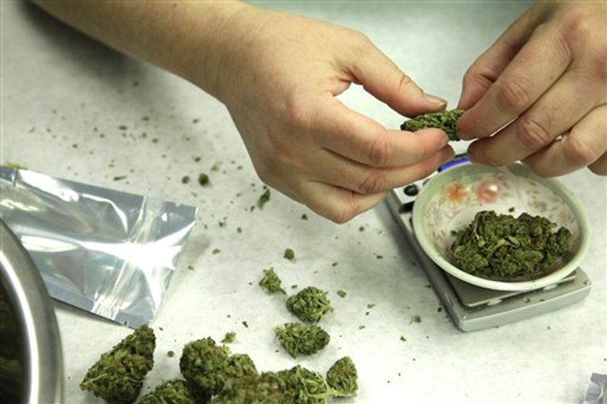 ** FILE ** In this Oct. 10, 2012, photo, marijuana is weighed and packaged for sale at the Northwest Patient Resource Center medical marijuana dispensary in Seattle. (Associated Press)