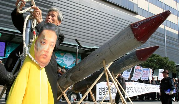 A South Korean protester hangs an effigy of North Korean leader Kim Jong-un near the North's mock missiles in Seoul on Tuesday, March 20, 2012, during an anti-North Korea rally denouncing the North's plan to launch a long-range rocket. North Korea vowed Sunday to go ahead with plans to launch the rocket, rejecting criticism in the West that it would scuttle recent diplomacy. (AP Photo/Lee Jin-man)