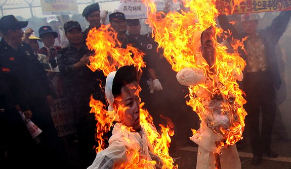 Protesters set fire to effigies of North Korean leader Kim Jong-un and South Korean activist No Su-hui during a rally denouncing Mr. No near the border village of Panmunjom, in Paju, South Korea, on Thursday, July 5, 2012.  South Korean police arrested Mr. No for making an extended trip to Pyongyang without government approval. (AP Photo/Hye Soo Nah)