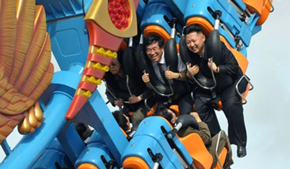 In this photo taken on Wednesday, July 25, 2012, and released by the Korean Central News Agency and distributed in Tokyo by the Korea News Service on Friday, July 27, 2012, North Korean leader Kim Jong-un (at right in the middle) reacts during a ride on an amusement-park attraction as he attends the completion ceremony of the Rungna People's Pleasure Ground in Pyongyang, North Korea. (AP Photo/Korean Central News Agency via Korea News Service)
