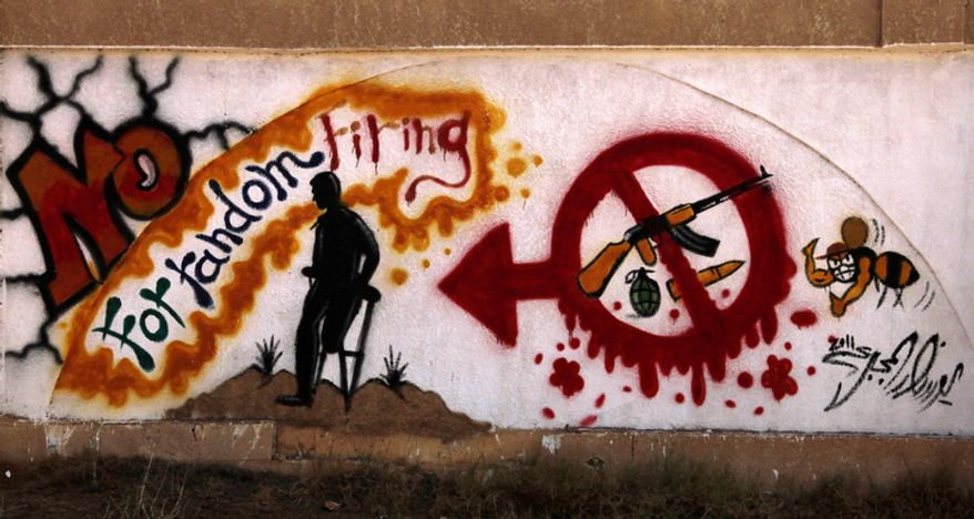 Graffiti on one of the city walls calls on people to stop random firing of weapons in Benghazi, Libya, on Saturday, Sept. 22, 2012. Leaders of tribes, which are the strongest social force in eastern Libya, have come forward to demand that the various armed militias disband. (AP Photo/Mohammad Hannon)
