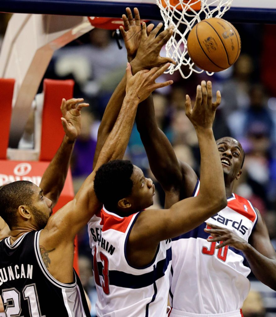 San Antonio Spurs forward Tim Duncan, and Washington Wizards forward Kevin Seraphin, and center Earl Barron go for the rebound in the first half of an NBA basketball game Monday, Nov. 26, 2012, in Washington.(AP Photo/Alex Brandon)