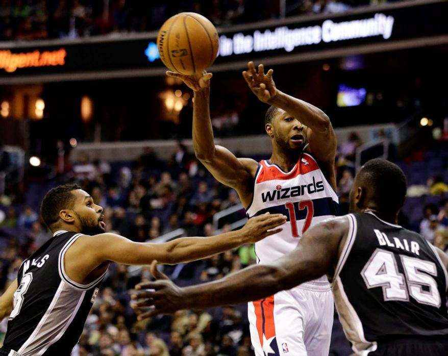 San Antonio Spurs guard Patty Mills (8), from Australia, and center DeJuan Blair (45) guard Washington Wizards guard A.J. Price (12) as he passes the ball in the first half of an NBA basketball game Monday, Nov. 26, 2012, in Washington. (AP Photo/Alex Brandon)