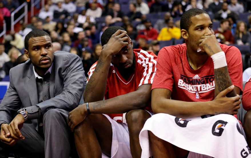 Washington Wizards forwards Trevor Booker, left, Martell Webster, and Trevor Ariza watch from the bench in the second half of an NBA basketball game against the San Antonio Spurs Monday, Nov. 26, 2012, in Washington. The Spurs won 118-92. The Wizards are now 0-12. (AP Photo/Alex Brandon)